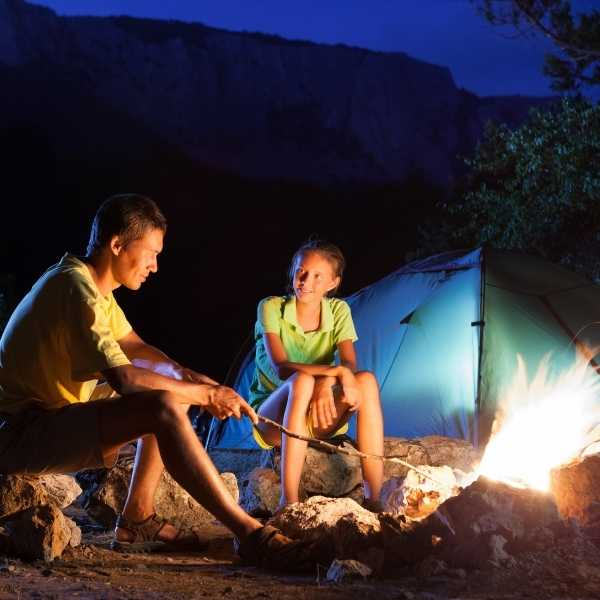 Father and daughter using campfire to keep mosquitoes away while camping